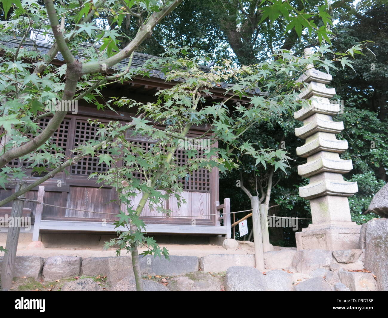 Photo at Korakuen Garden, one of the Three Great Gardens of Japan; a bench by a stone tower provides a shady spot to relax underneath the maples - Stock Image