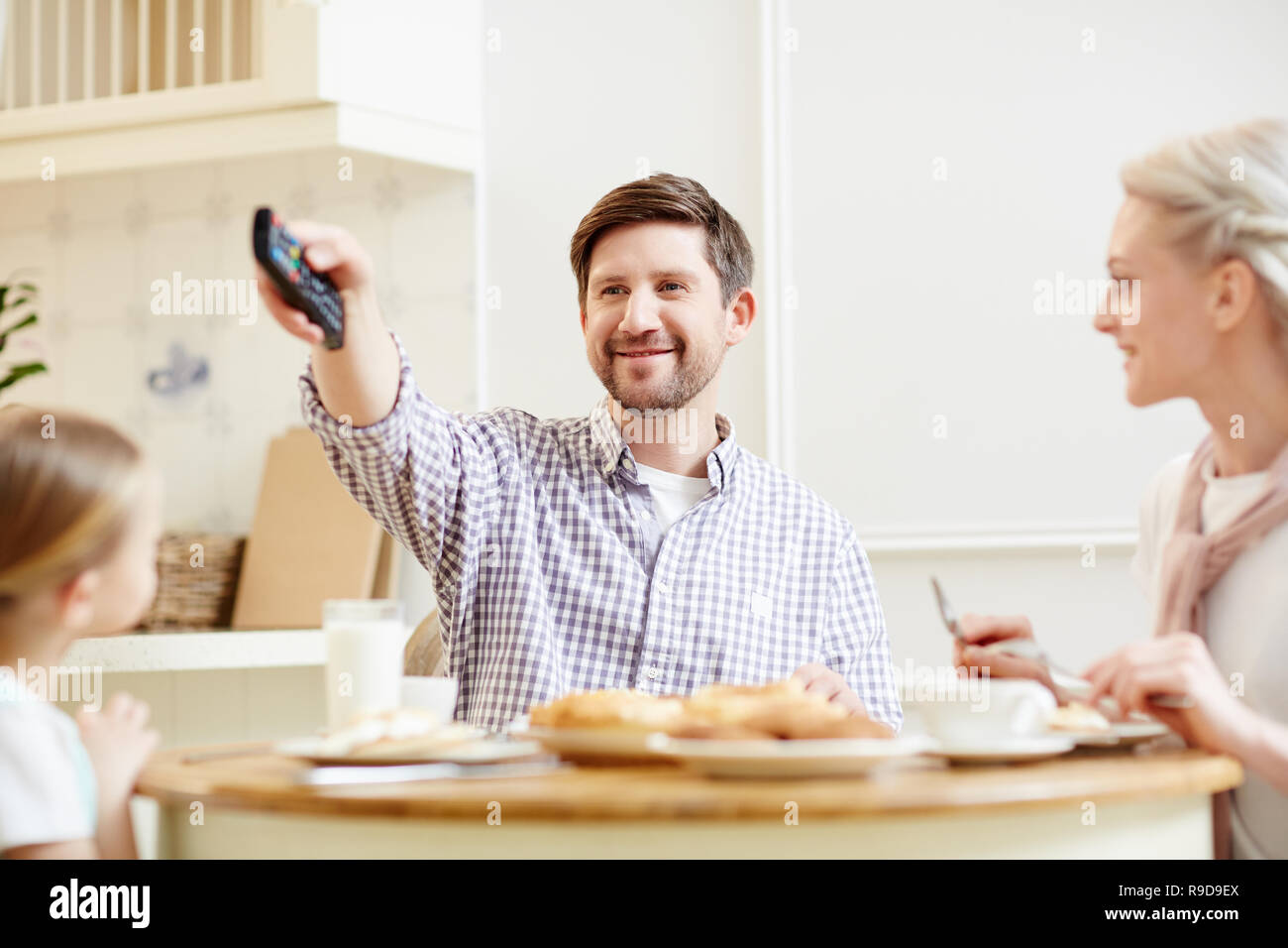 Watching tv at family dinner - Stock Image