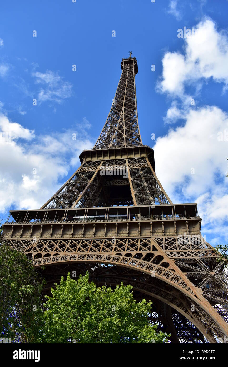 Eiffel Tower, perspective from below. Paris, France. Trees and blue sky with clouds. - Stock Image