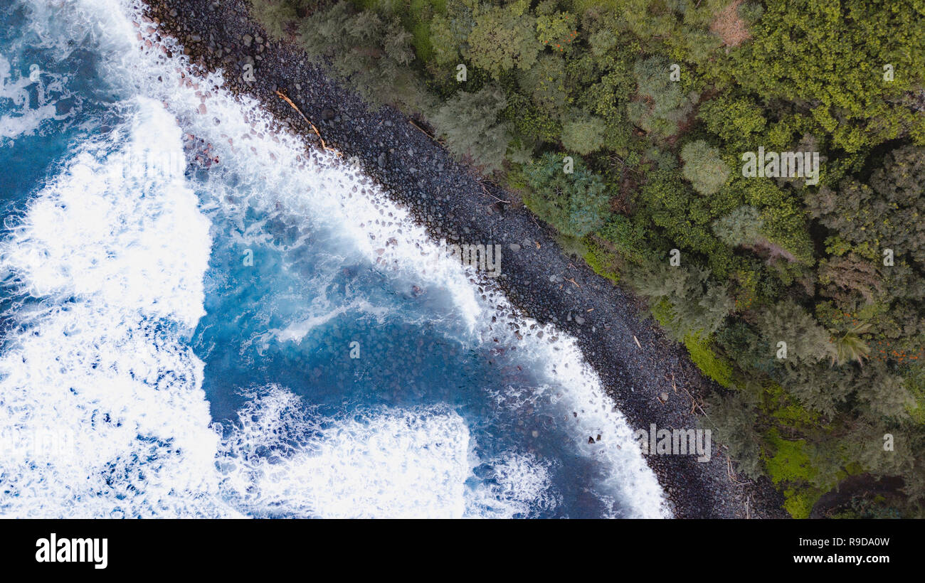 Overhead shots of waves crashing onto a black sand beach on the big island of Hawaii - Stock Image