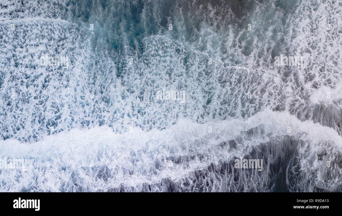 Overhead shots of waves crashing onto a black sand beach on the big island of Hawaii Stock Photo