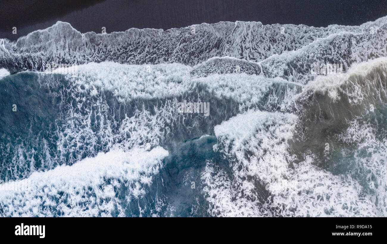 Overhead shots of waves crashing onto a black sand beach on the big island of Hawaii Stock Photo