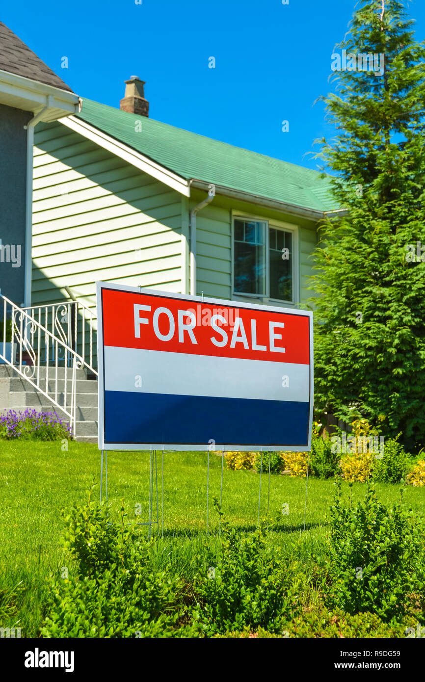 Real estate sign 'For Sale' on front yard of a house - Stock Image