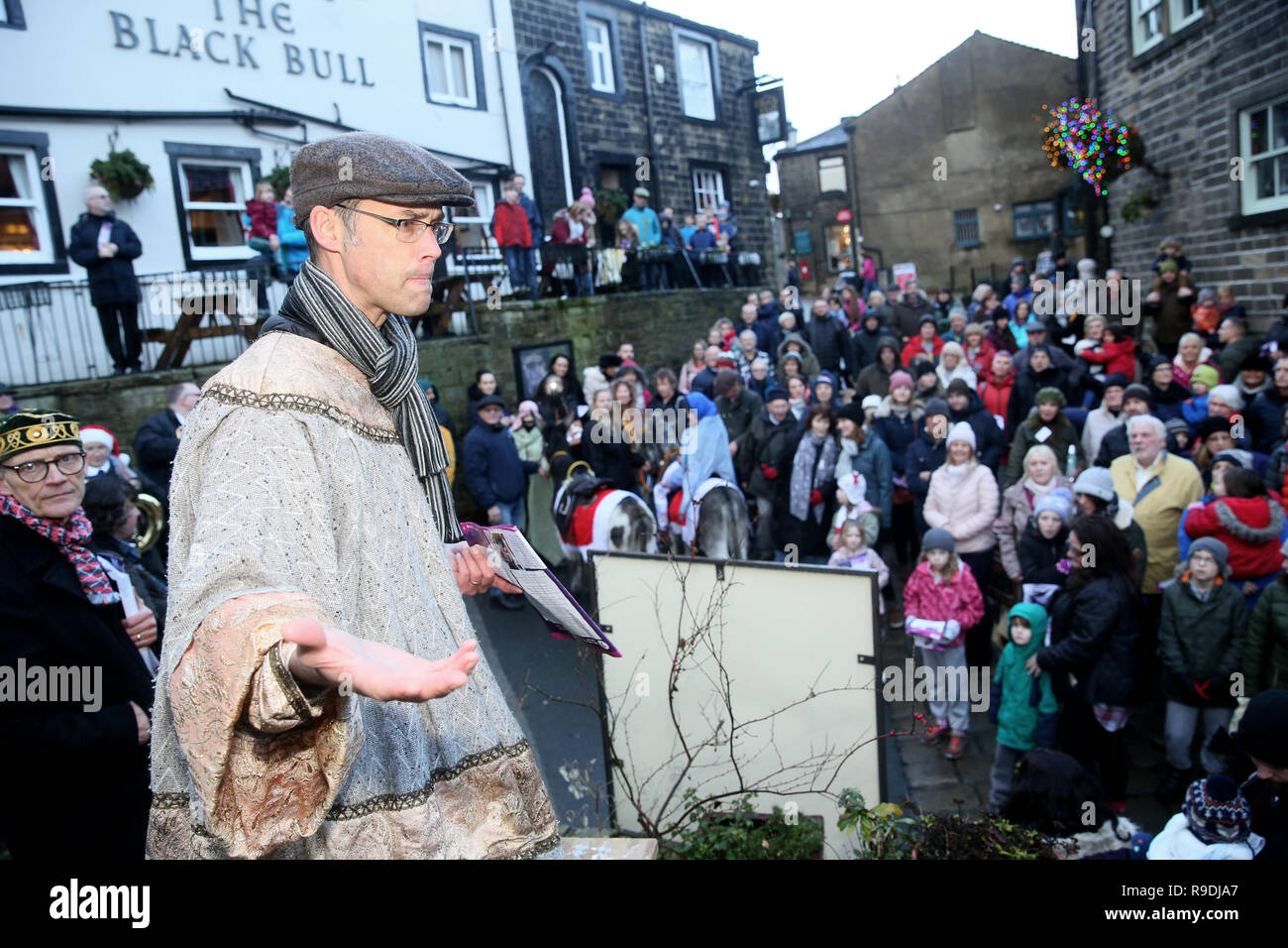 Haworth, Bradford, UK. 22nd Dec 2018. A traditional nativity re-enactment with children playing the parts of Mary and Joseph for the magical nativity procession through  Main Street.  Mary rides on a Donkey and Joseph knocks on the doors of local shops and Inns asking for a room for the night.  True to the narrative they are turned away with a 'no room at the Inn' reply.  A narrator guides the towns visitors through the story and a brass band provide backing for the singing of carols.  Haworth,Bradford, UK, 22nd December 2018 (C)Barbara Cook/Alamy Live News Credit: Barbara Cook/Alamy Live News - Stock Image