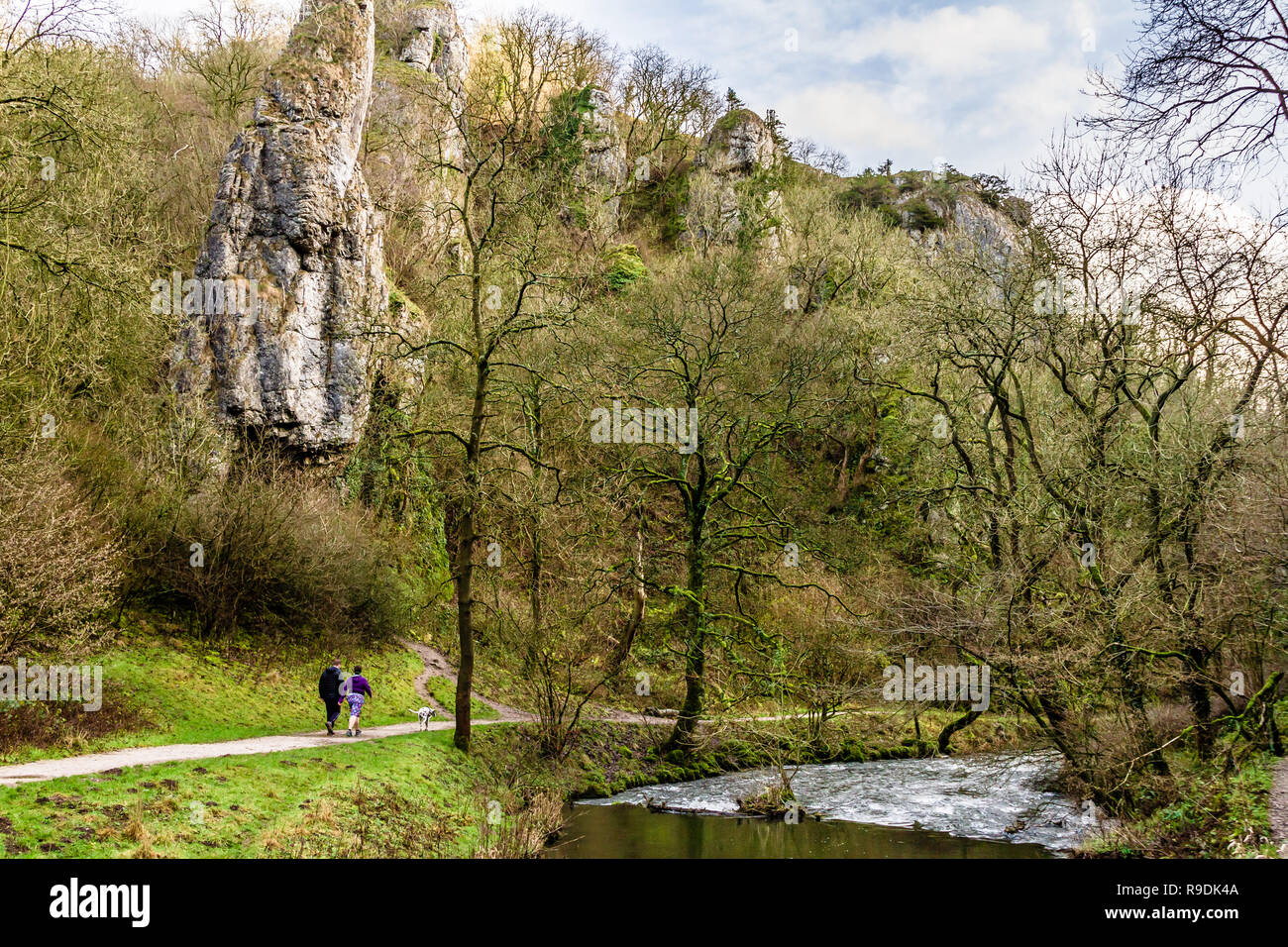 A couple walk their dog beside the River Dove in Dovedale during an unusually mild winter day. Peak District National Park, UK. 22nd December 2018. - Stock Image