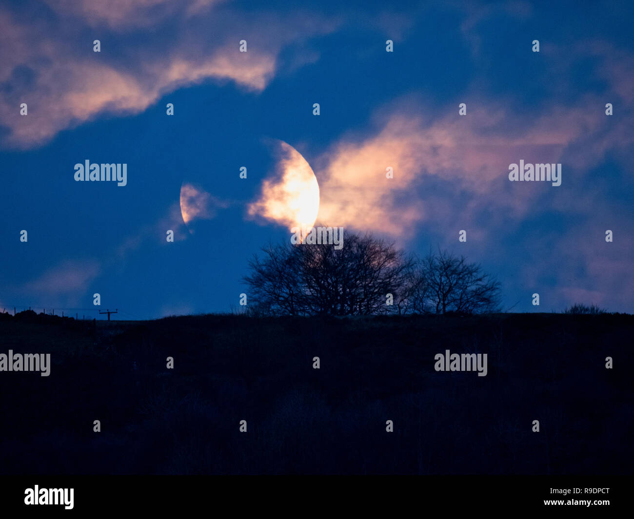 Wirksworth, UK. 22nd Dec, 2018. UK Weather: Winter Solstice Full Moon rising in between the clouds over Cromford Moor, Bolehill taken from the StarDisc above Wirksworth in the Derbyshire Dales Credit: Doug Blane/Alamy Live News - Stock Image