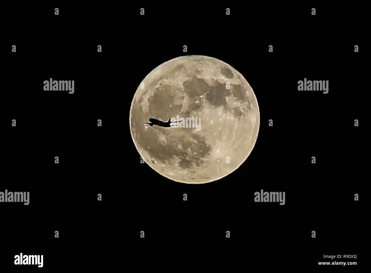 An airplane flies in front of Winter Solstice Moon over London. December's full moon has earned the nickname of the Cold Moon which falls shortly after Friday's winter solstice and the peak of the Ursid Meteor Shower - the activity that begins annually around December 17 and runs for a week plus, until the 25th or 26th. - Stock Image