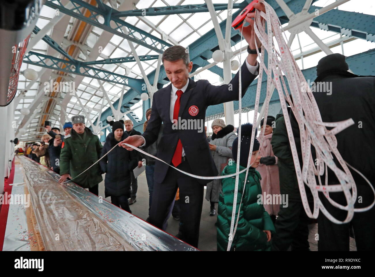 Moscow, Russia. 23rd Dec, 2018.  Measuring halva prepared by cooks from the 7 North Caucasus regions on the Bogdan Khmelnitsky Bridge. The 65.5-metre long confection weighing 570 kg has entered the Russian Book of Records as the largest.  Credit: ITAR-TASS News Agency/Alamy Live News - Stock Image