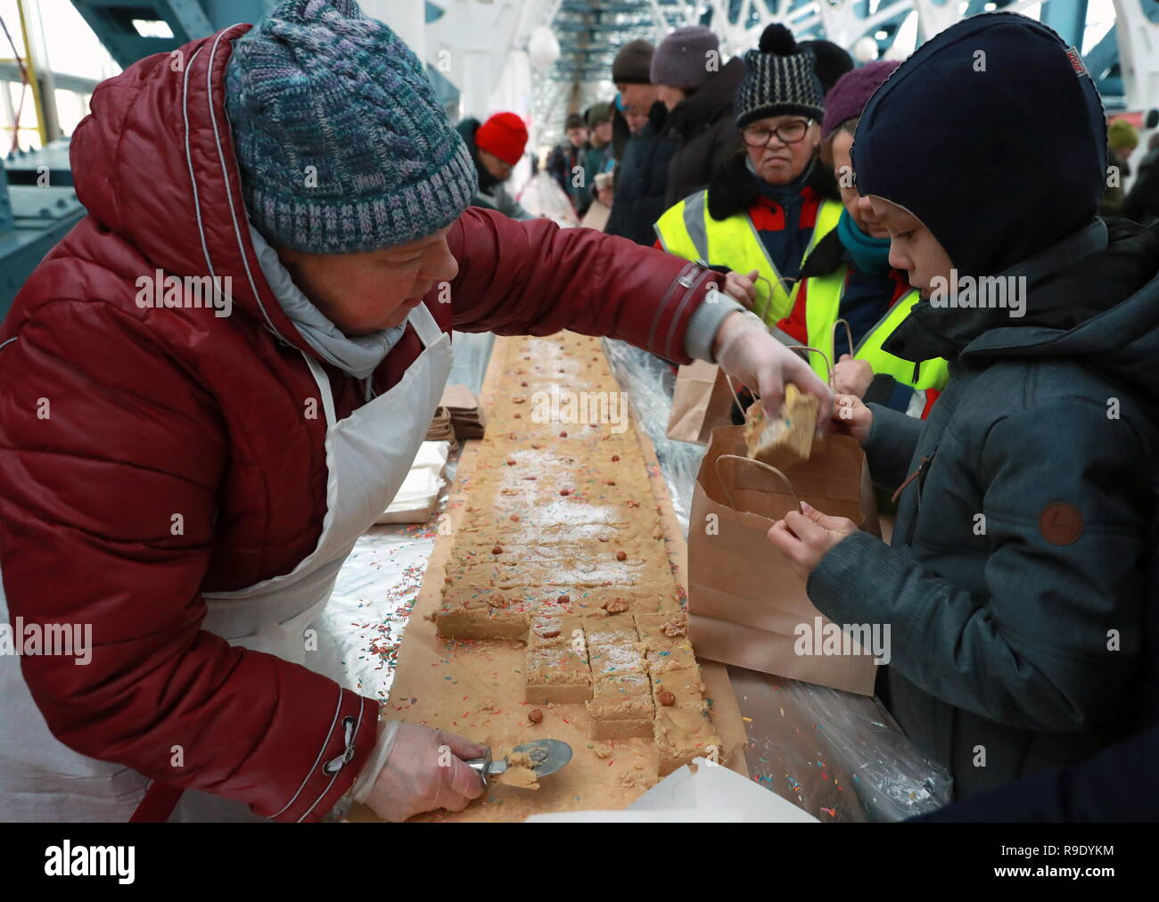 Moscow, Russia. 23rd Dec, 2018.  Halva prepared by cooks from the 7 North Caucasus regions on the Bogdan Khmelnitsky Bridge. The 65.5-metre long confection weighing 570 kg has entered the Russian Book of Records as the largest.  Credit: ITAR-TASS News Agency/Alamy Live News - Stock Image