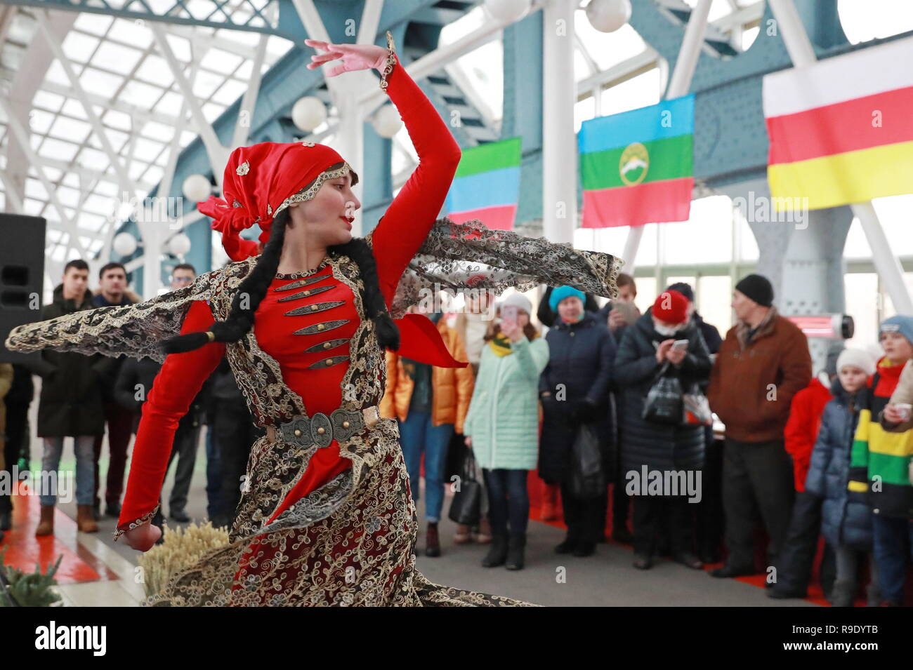 Moscow, Russia. 23rd Dec, 2018.  A woman in a tradition dress dancing during a ceremony to measure halva prepared by cooks from the 7 North Caucasus regions on the Bogdan Khmelnitsky Bridge. The 65.5-metre long confection weighing 570 kg has entered the Russian Book of Records as the largest.  Credit: ITAR-TASS News Agency/Alamy Live News - Stock Image