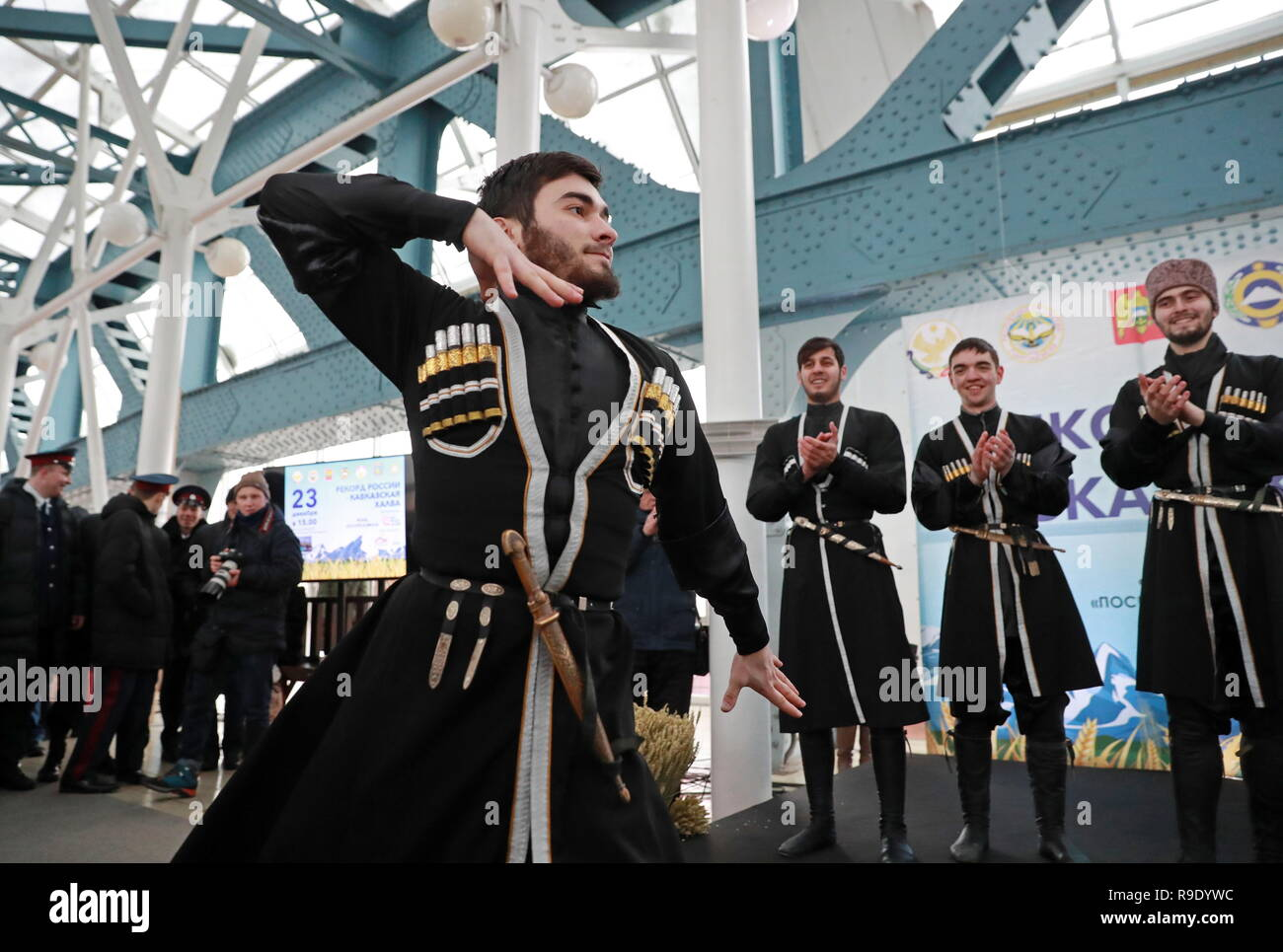 Moscow, Russia. 23rd Dec, 2018.  A man in a tradition dress dancing during a ceremony to measure halva prepared by cooks from the 7 North Caucasus regions on the Bogdan Khmelnitsky Bridge. The 65.5-metre long confection weighing 570 kg has entered the Russian Book of Records as the largest.  Credit: ITAR-TASS News Agency/Alamy Live News - Stock Image