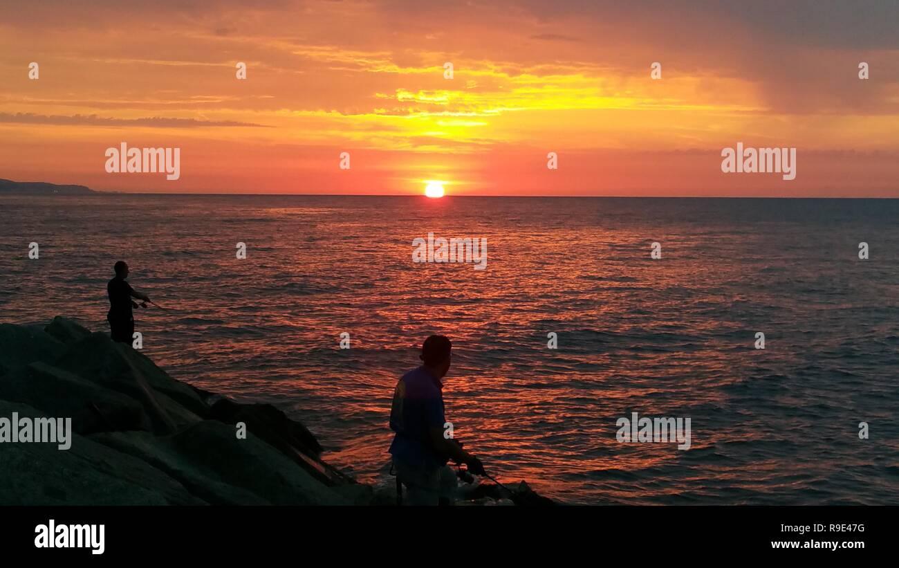 Two fishermen looking sunrise Stock Photo
