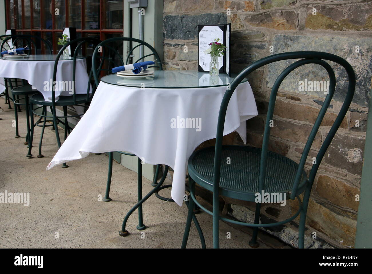 The outdoor cafe has white tablecloths. - Stock Image