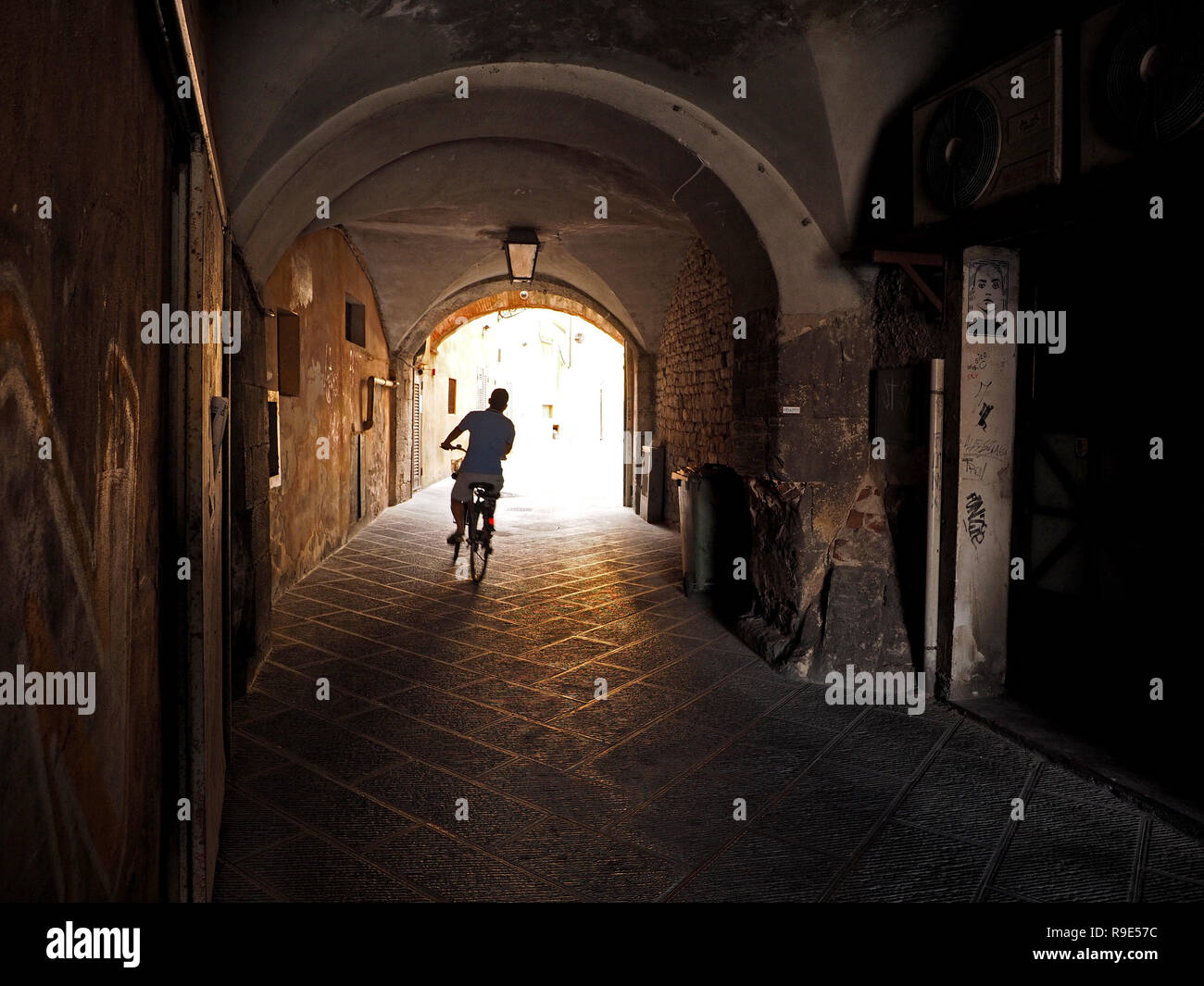 silhouetted single cyclist careers towards the light along a stone-paved alleyway through vaulted tunnel between city centre buildings in Pisa, Italy - Stock Image