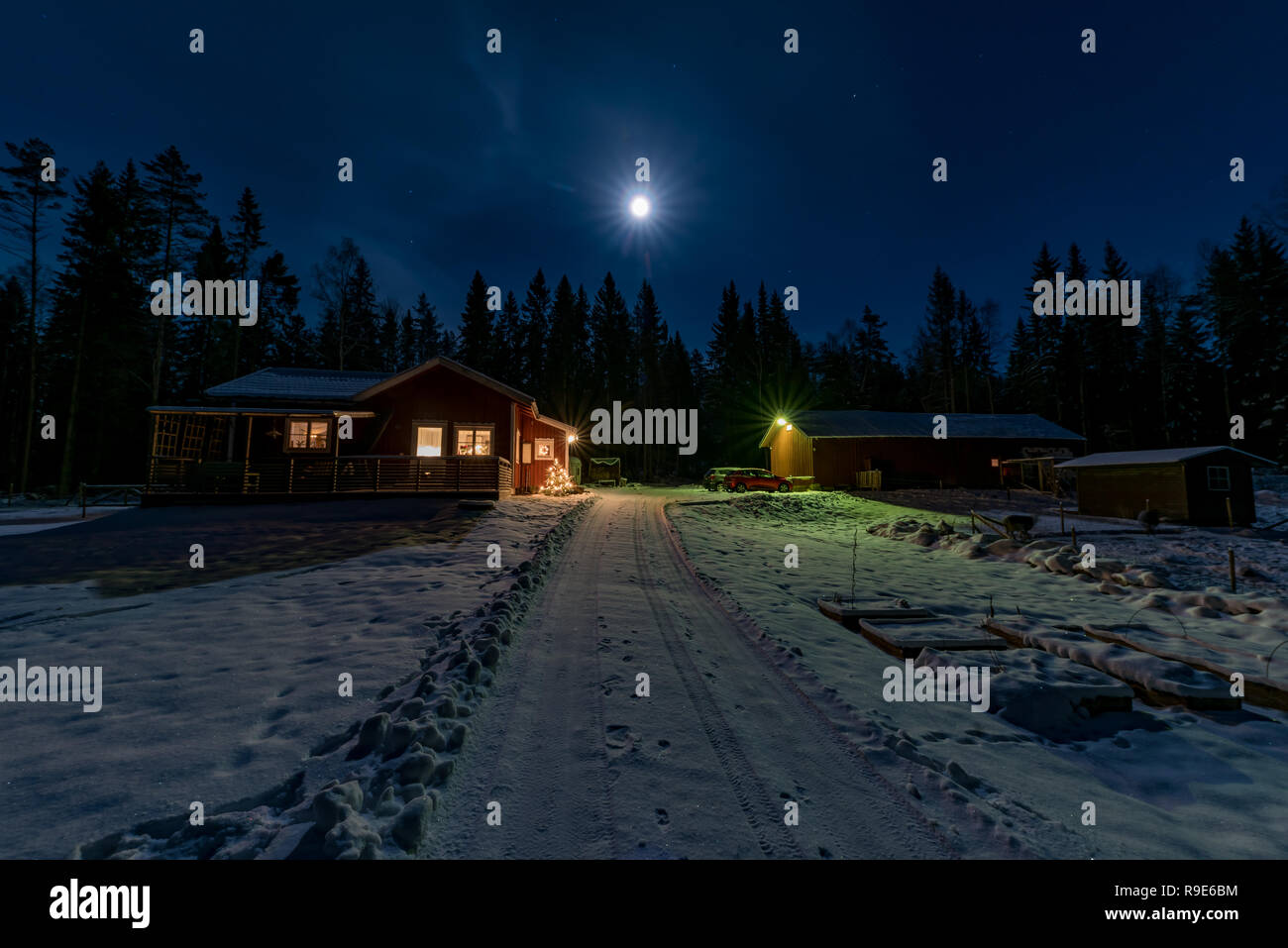 red little cabin in moon light and snow december 22 2018 - Stock Image
