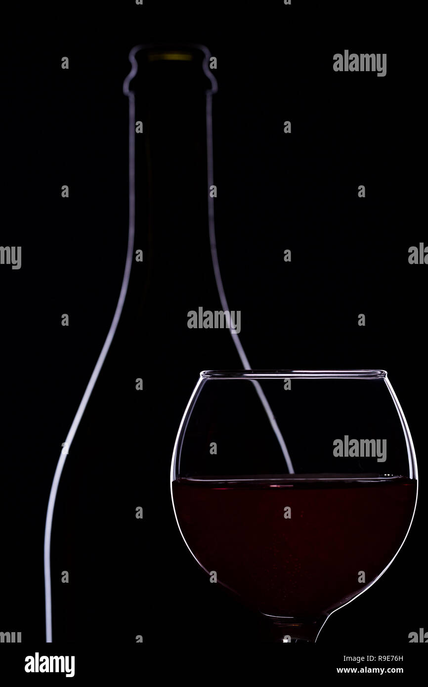 0914859261b17f Red wine in wine glasses and wine bottle on a black background ...
