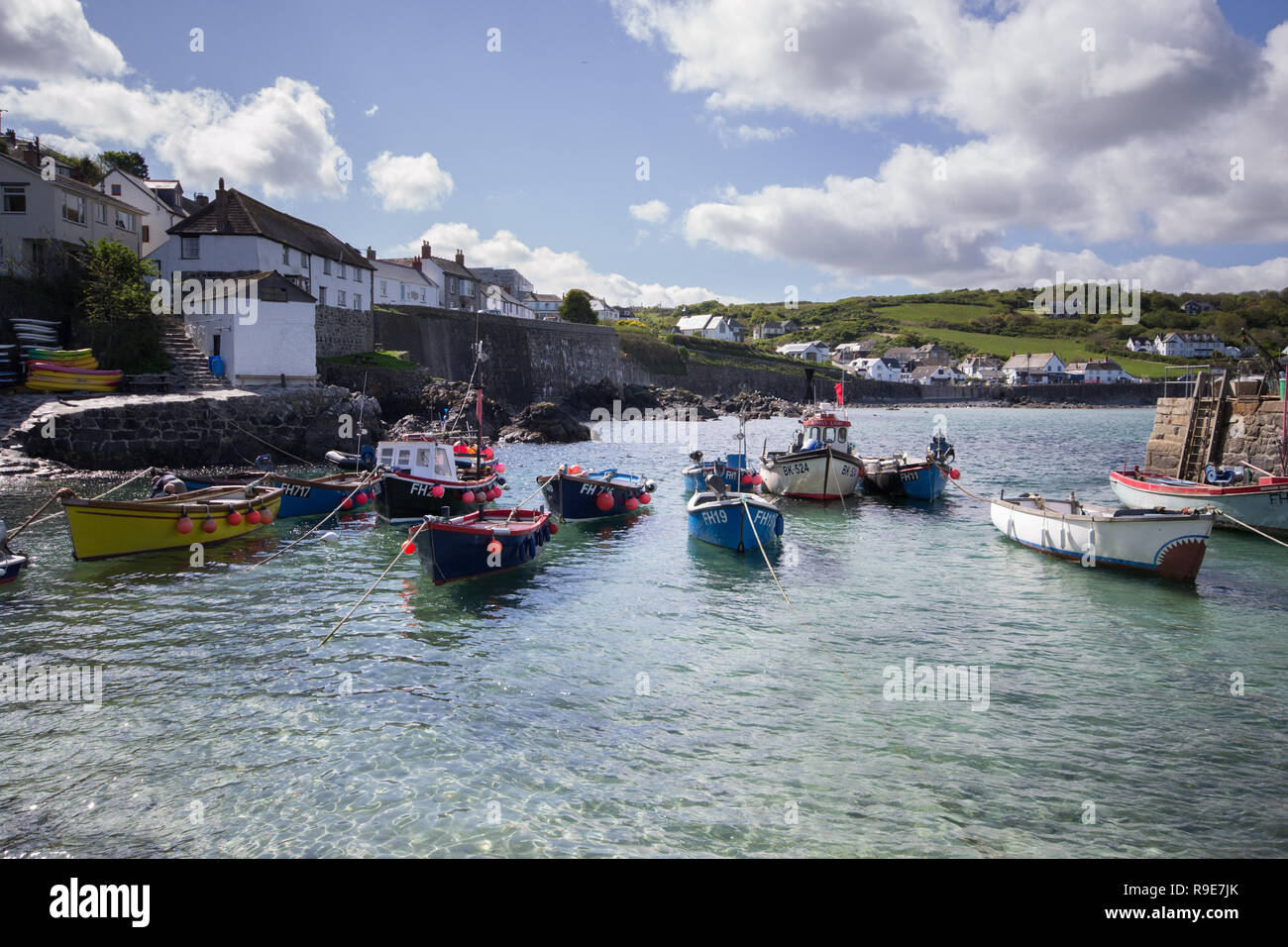 Moored boats in the clear water at Coverack Harbour in Cornwall - Stock Image