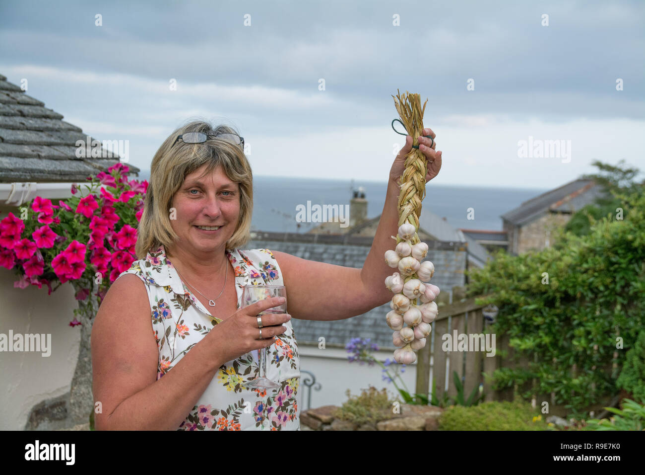 Woman holding up a string of plaited garlic that she has just made holding a glass of wine - Stock Image