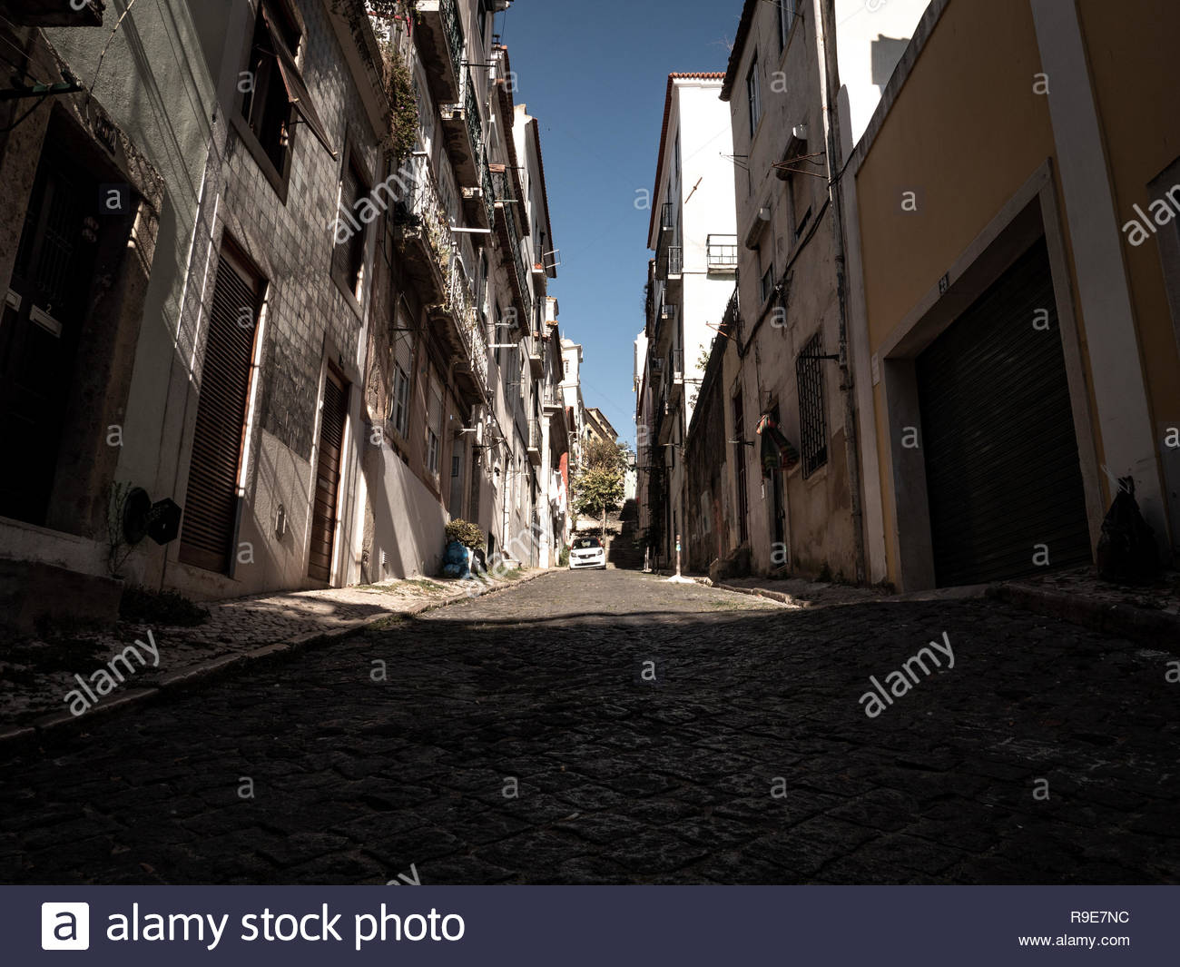 Stone street in historical downtown of Lisbon, Europe with buildings. There are no people in the alley. Great place for travel on holiday / vacation - Stock Image