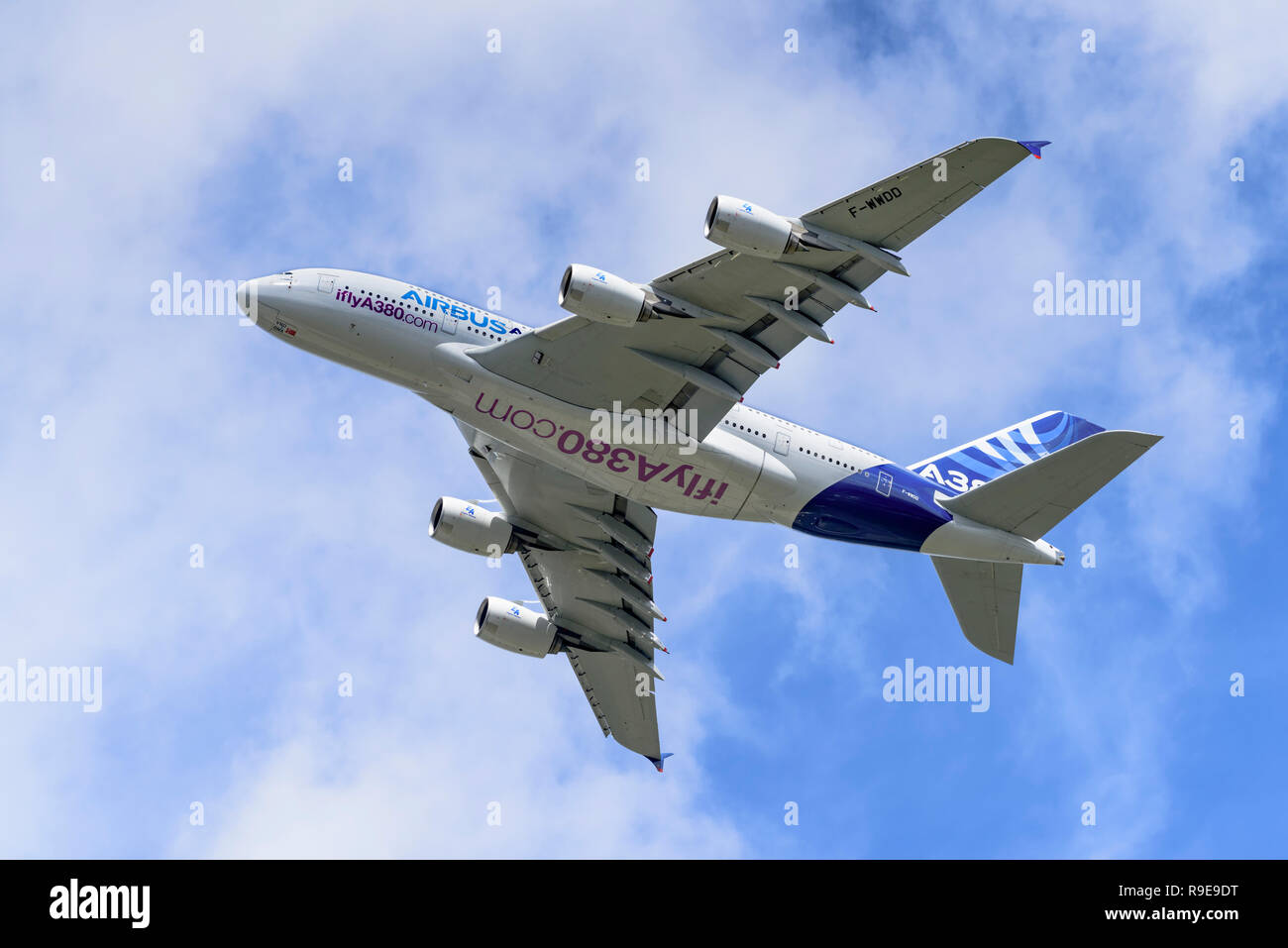 Airbus A380 passenger airliner shows its underside and flight control surfaces during a clean pass from right to left. - Stock Image