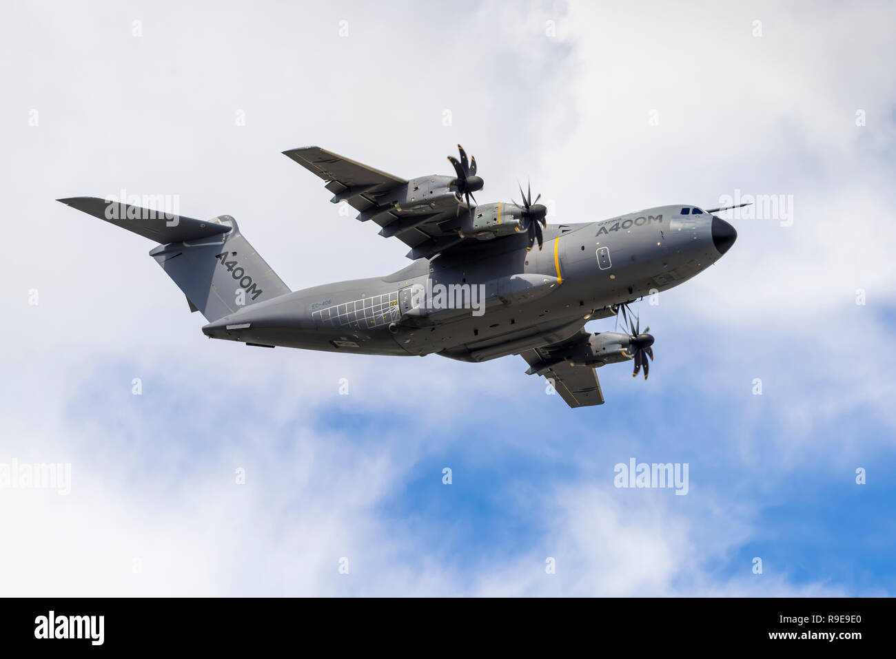 Airbus A400M Atlas military transport aircraft performs a clean pass (wheels up), flying overhead from left to right. - Stock Image