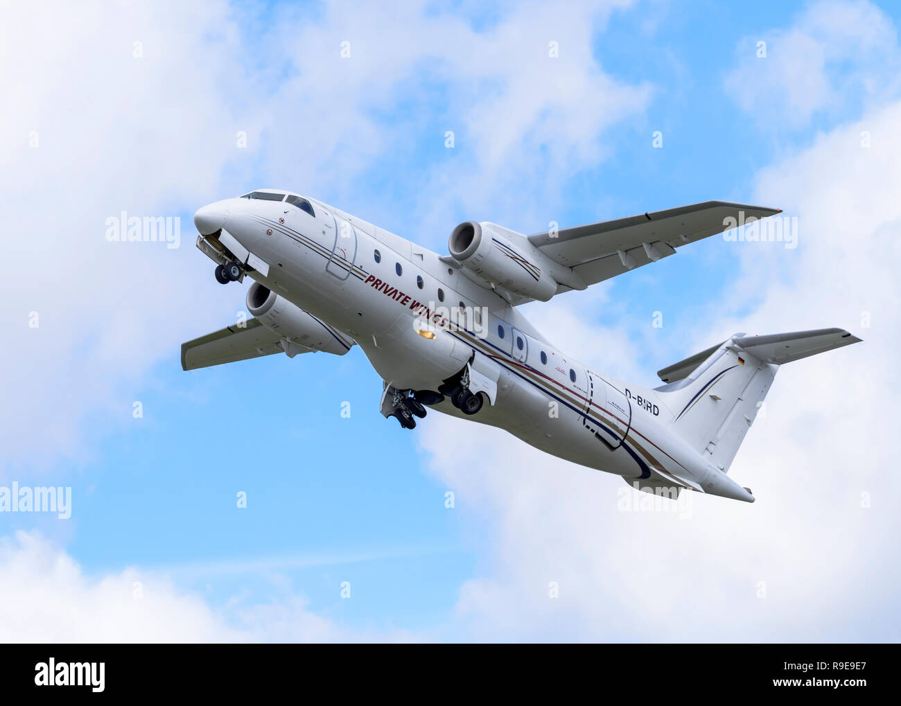 Fairchild-Dornier 328JET commuter airliner, in Private Wings Flugcharter livery, retracts its wheels after take-off. - Stock Image