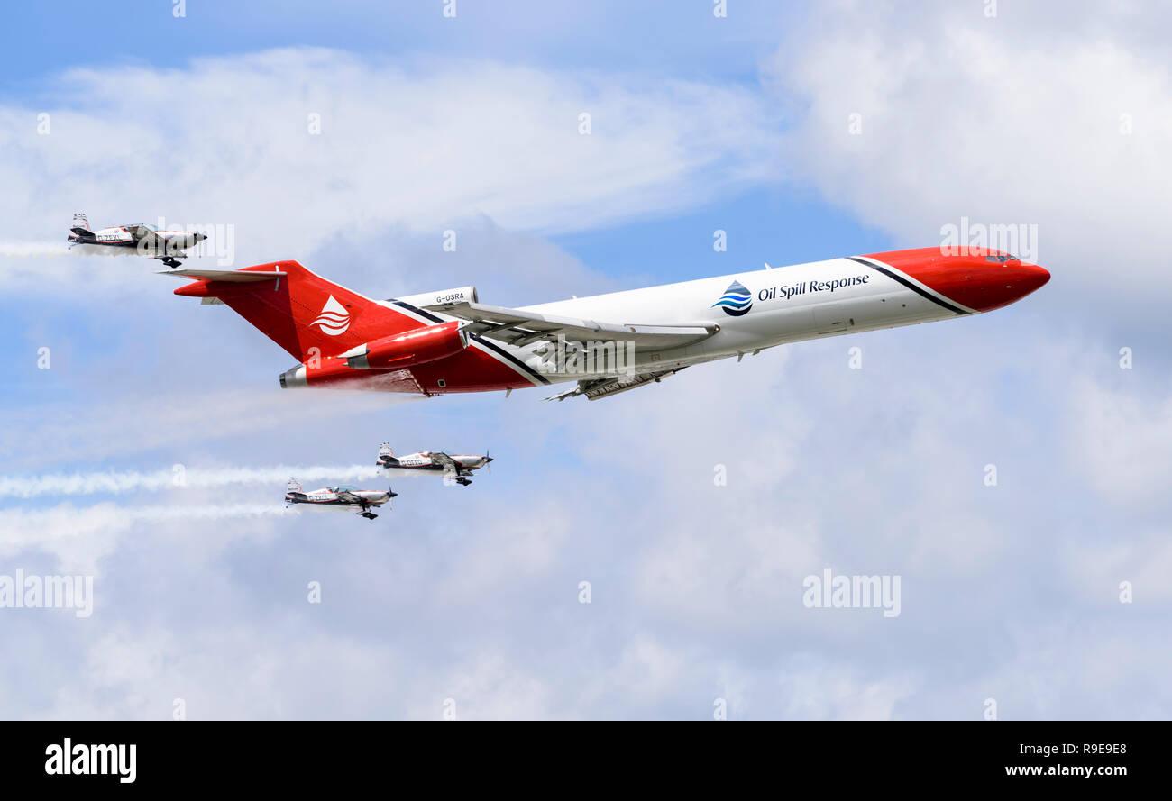 Boeing 727-2S2F (RE) Oil Spill Response aircraft (accompanied by three Extra 300LPs) uses water to simulate the oil dispersant spray boom in action. - Stock Image