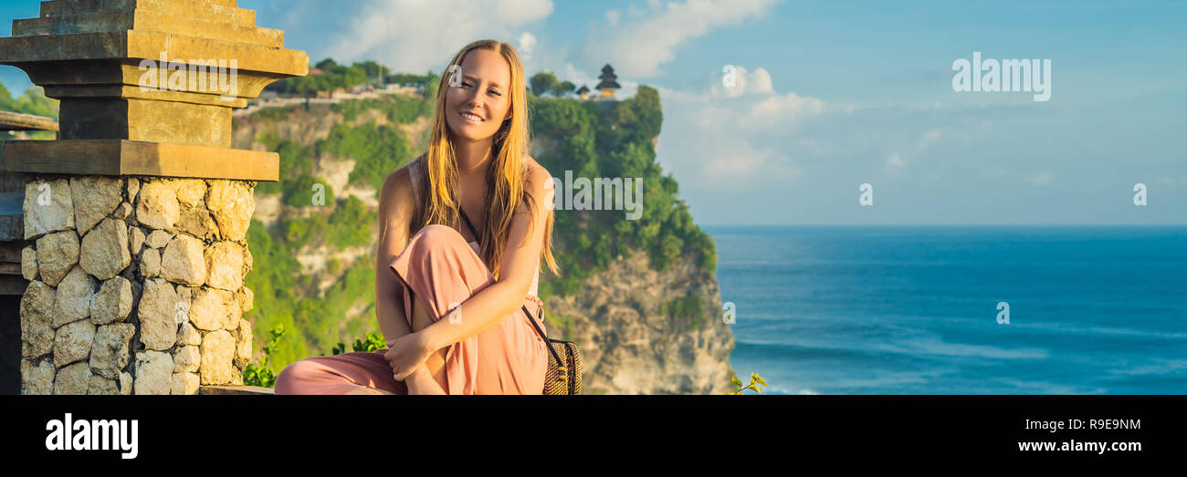 Young woman traveler in Pura Luhur Uluwatu temple, Bali, Indonesia. Amazing landscape - cliff with blue sky and sea BANNER, LONG FORMAT - Stock Image