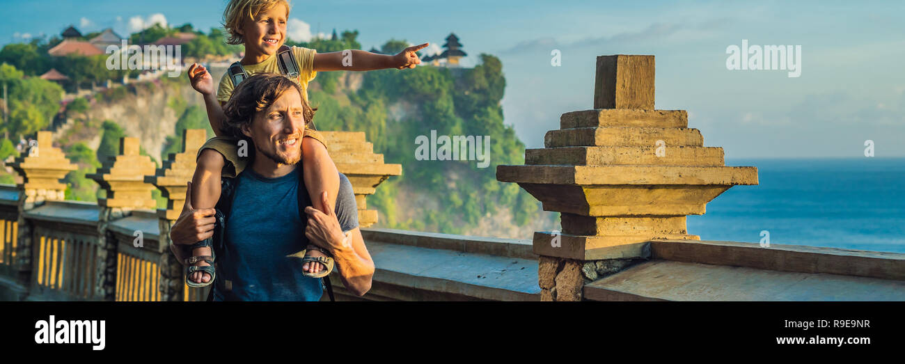 Dad and son travelers in Pura Luhur Uluwatu temple, Bali, Indonesia. Amazing landscape - cliff with blue sky and sea. Traveling with kids concept BANNER, LONG FORMAT - Stock Image