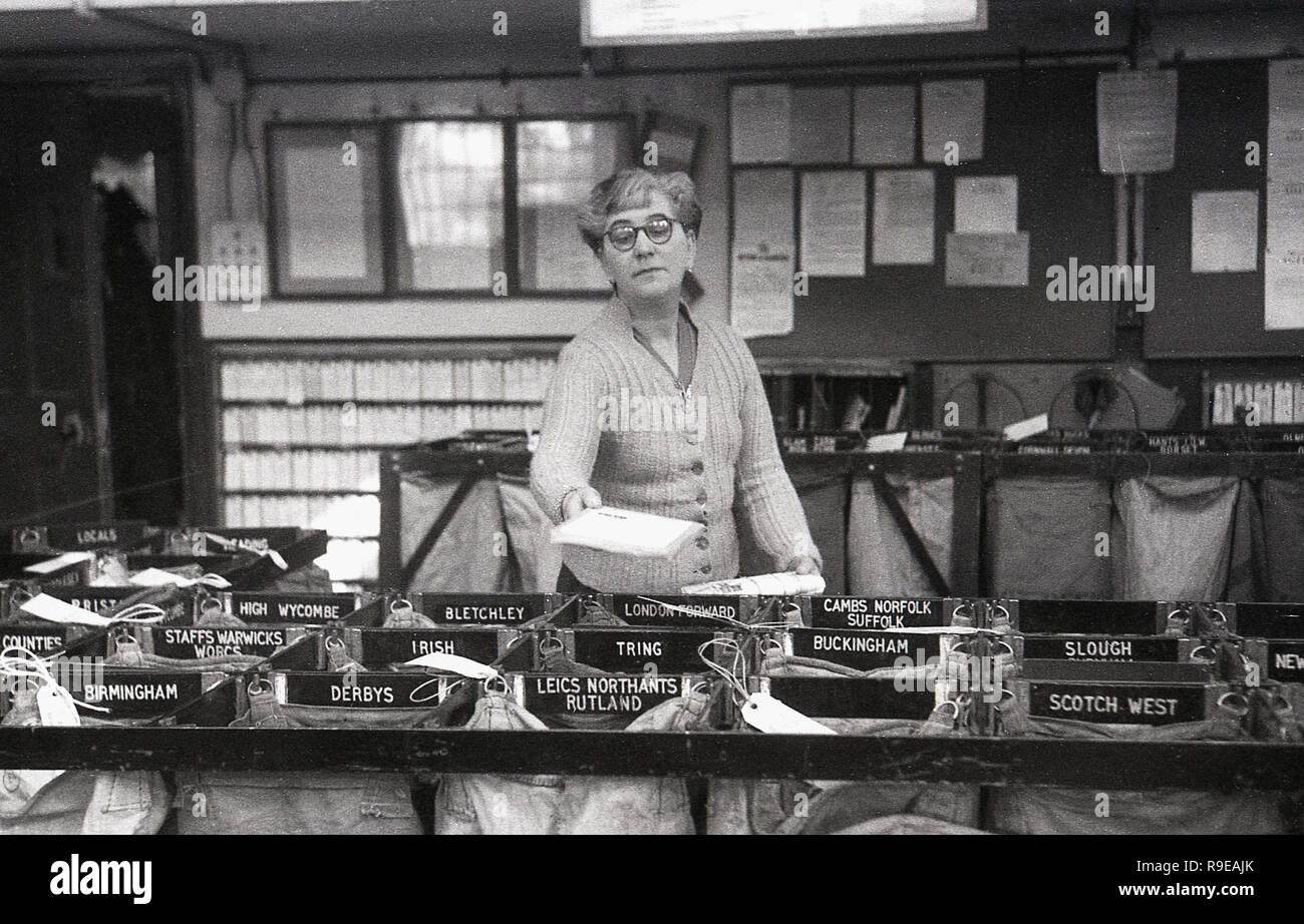 1948, inside a Royal Mail postal sorting office, picture shows a female worker putting letters into individual sacks for the different towns and regions of the UK. - Stock Image