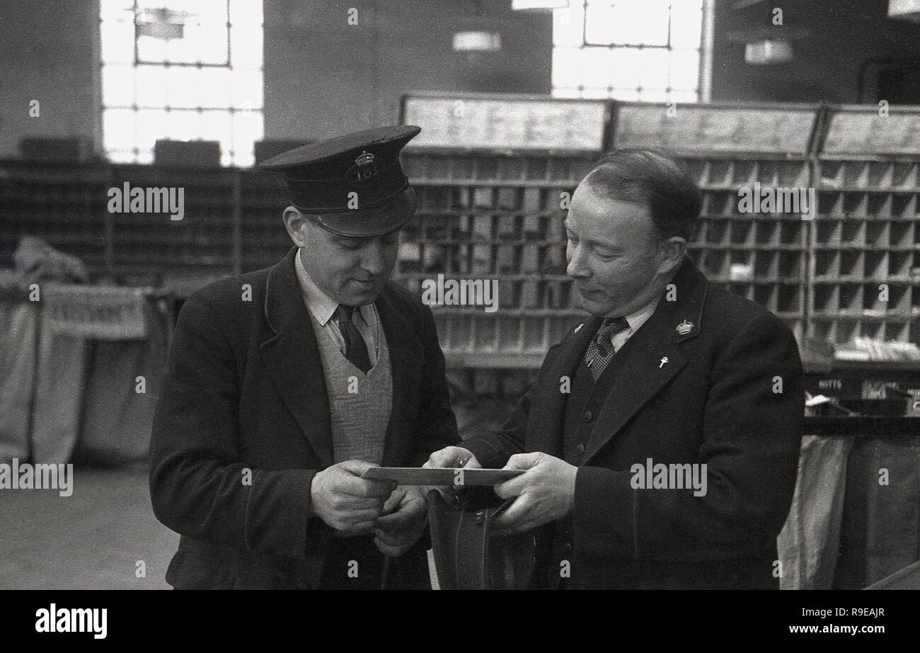 1948, picture shows two uniformed Royal Mail staff inside a postal sorting office, England, UK, a postman with cap standing with his supervisor checking the address on a letter. - Stock Image