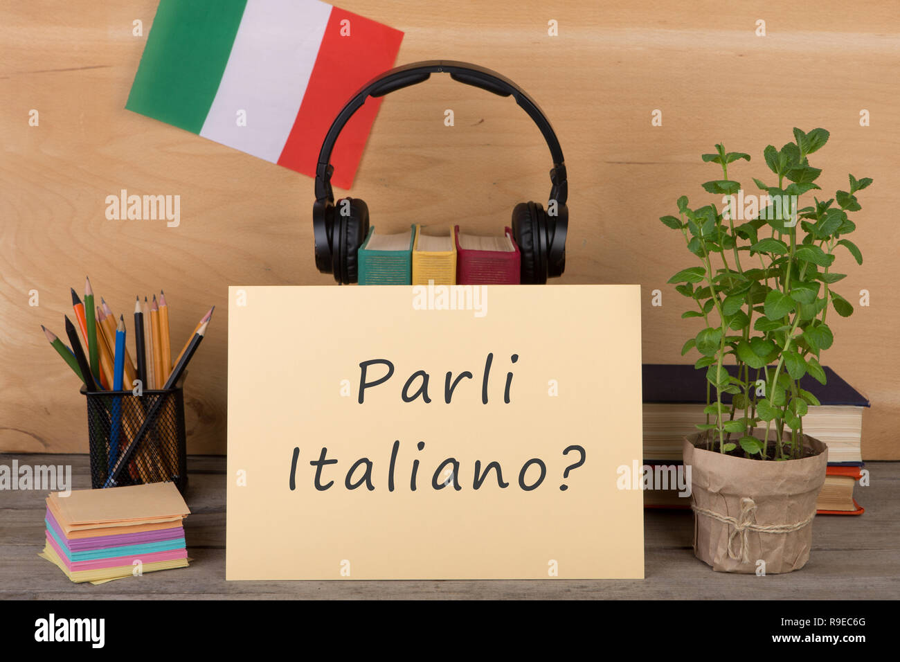 Learning languages concept - paper with text 'parli italiano?', flag of the Italia, books, headphones, pencils on wooden background - Stock Image
