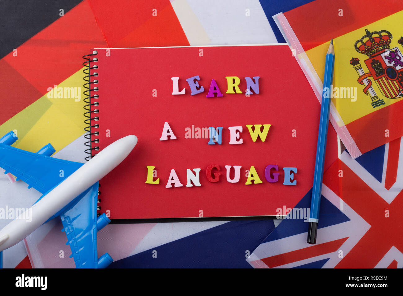 Learning languages concept - red notepad and colorful wooden letters with text 'Learn a new language', flags, model airplane, pencil - Stock Image