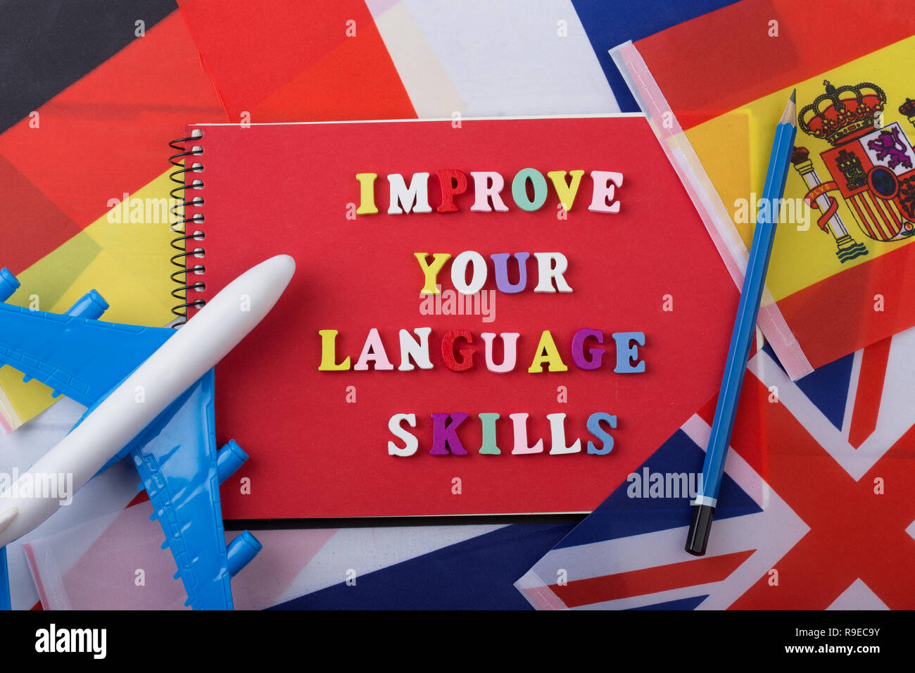 Learning languages concept - red notepad and colorful wooden letters with text 'Improve your language skills', flags, model airplane, pencil - Stock Image