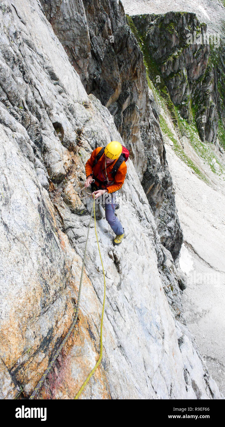 rock climber on a hard alpine route in the Alps of Switzerland placing mobile protection - Stock Image