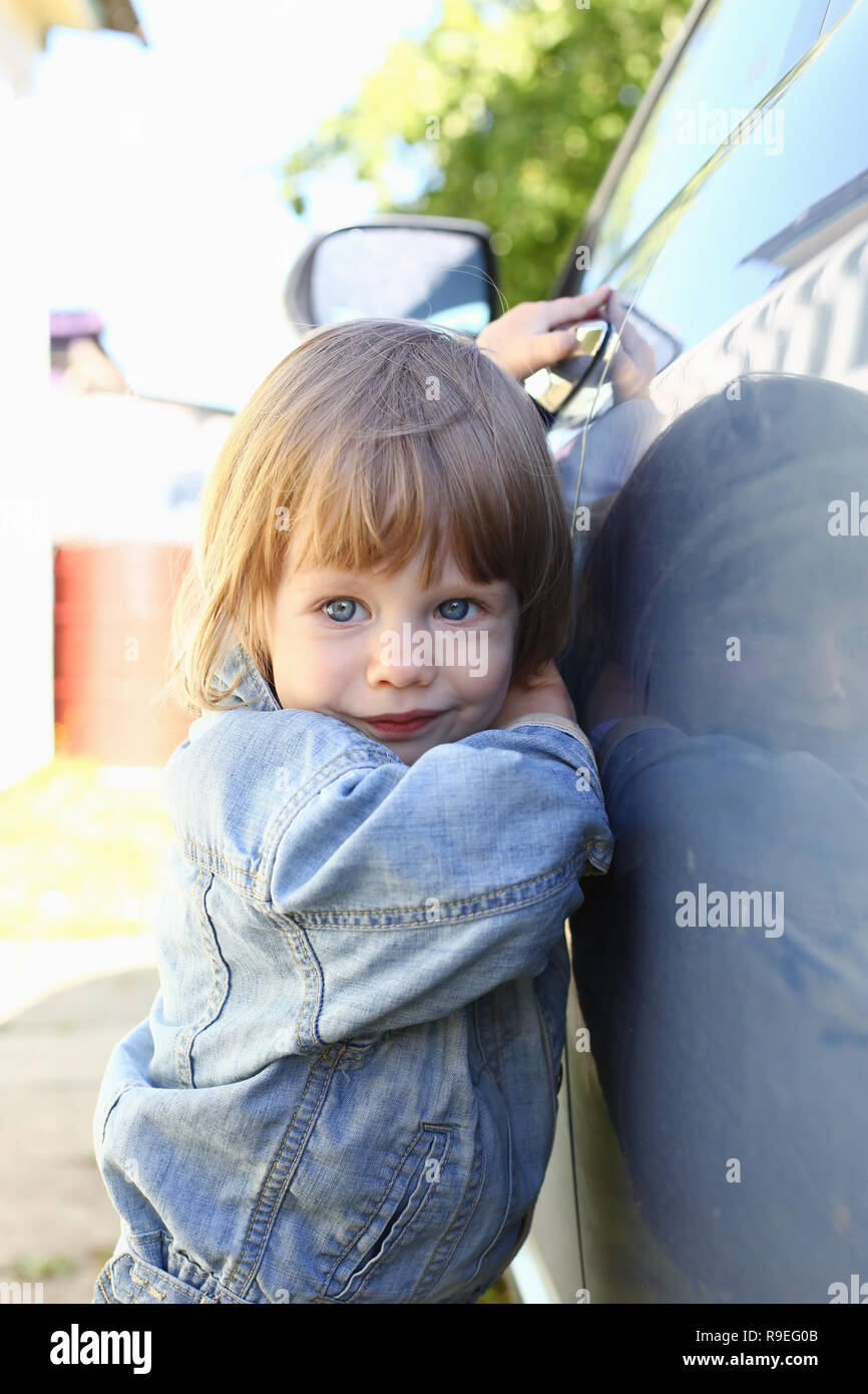 Little fashion child holds the car handle in a jeans jacket Stock Photo