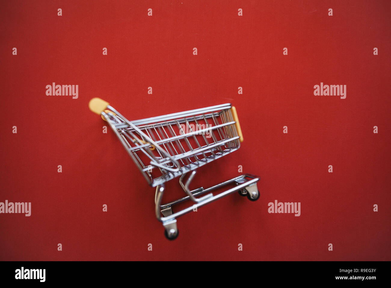 Empty shopping trolley on a red background. - Stock Image