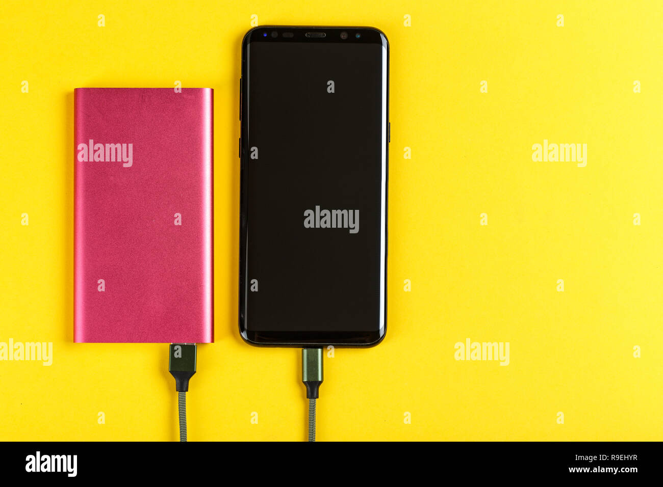 the smartphone is charging from a pink power bank on a yellow background Stock Photo