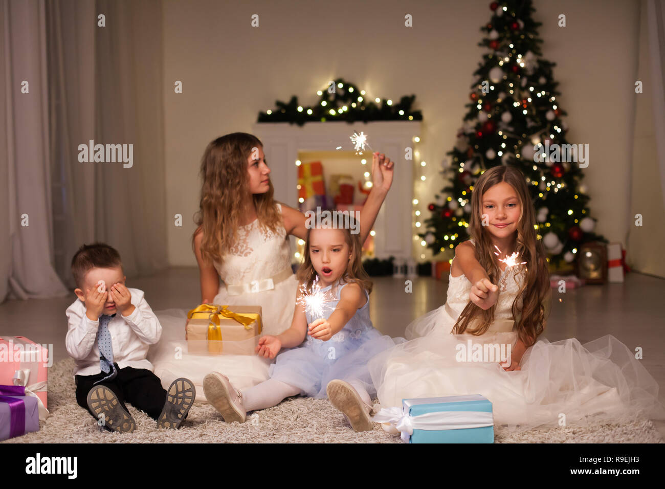 Kids open Christmas presents new year holiday lights sparklers Stock Photo