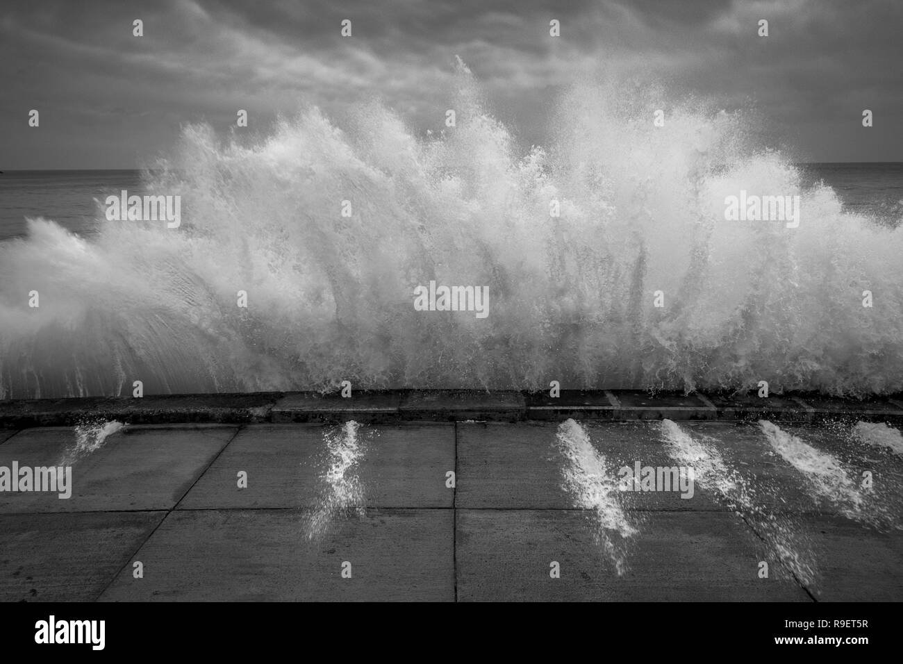 Scarborough seafront: Dramatic wave crashing against the sea wall in black and white - Stock Image