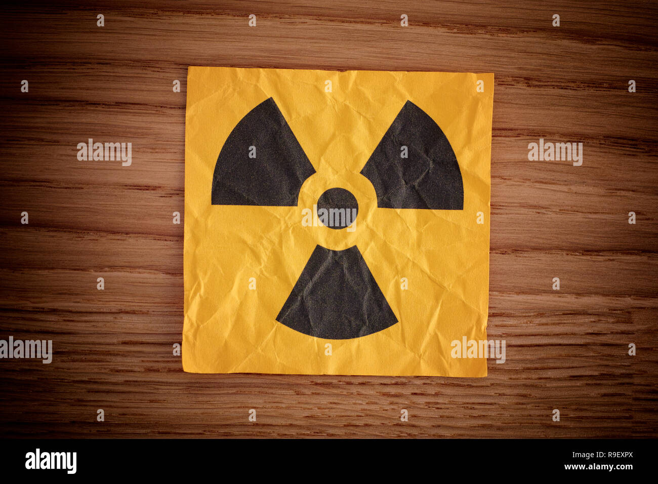 Radiation warning sign on a wooden board. Close up. - Stock Image