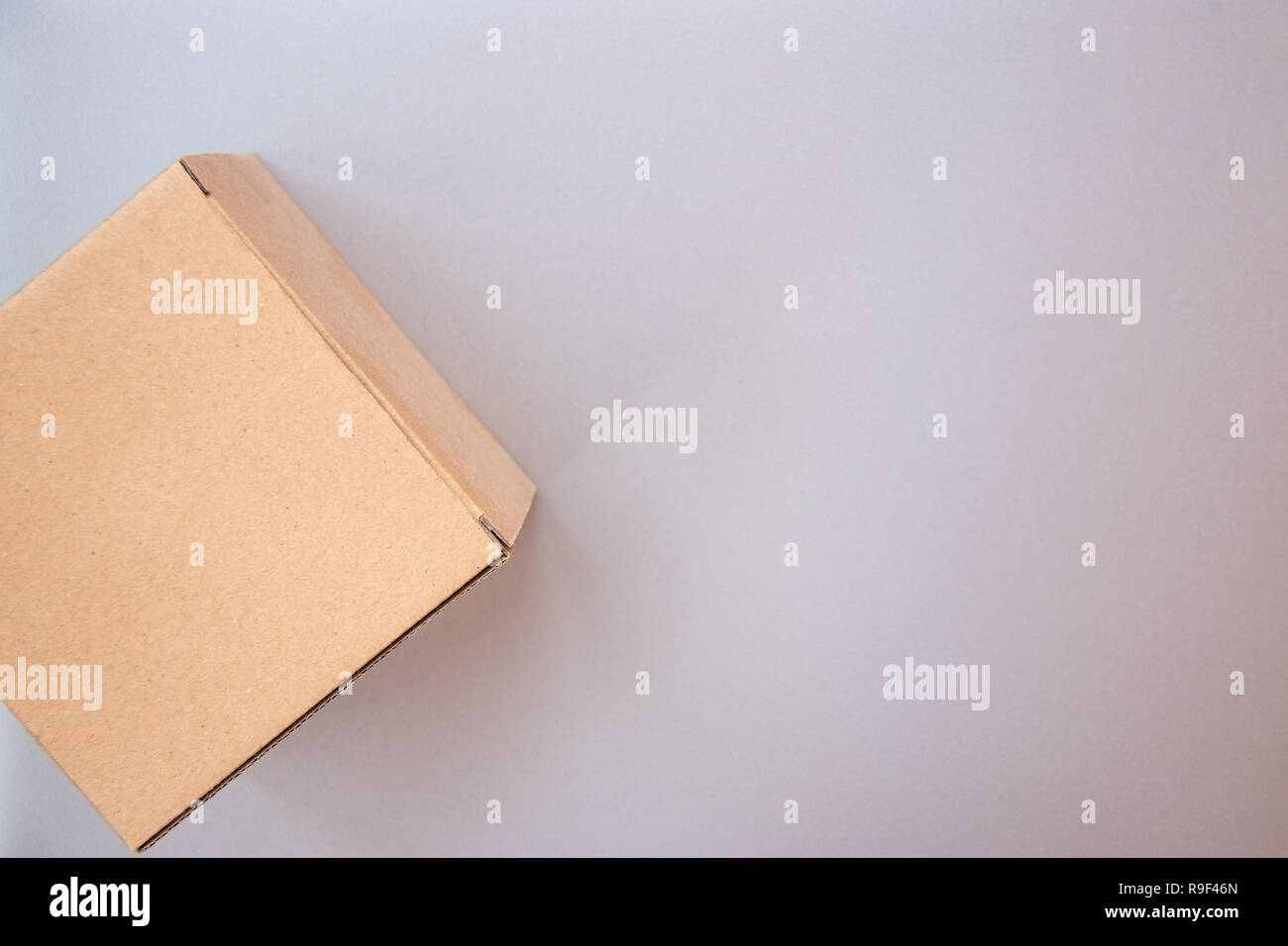 Corner of closed big square cardboard craft gift box on the silver gray metal background - Stock Image