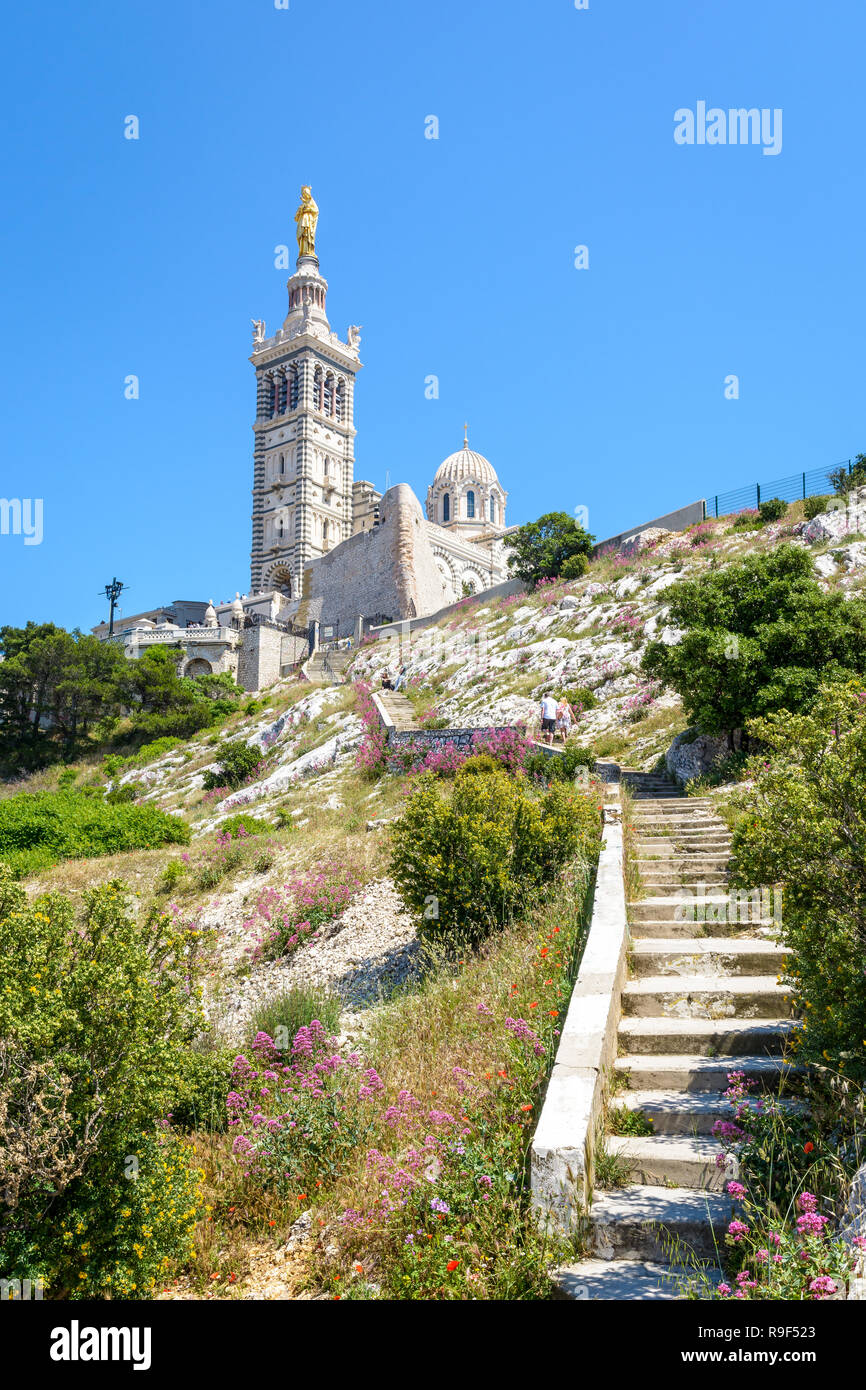 Low angle view of Notre-Dame de la Garde basilica on top of the hill in Marseille, France, seen from a secondary access trail with stairs in the rocks - Stock Image