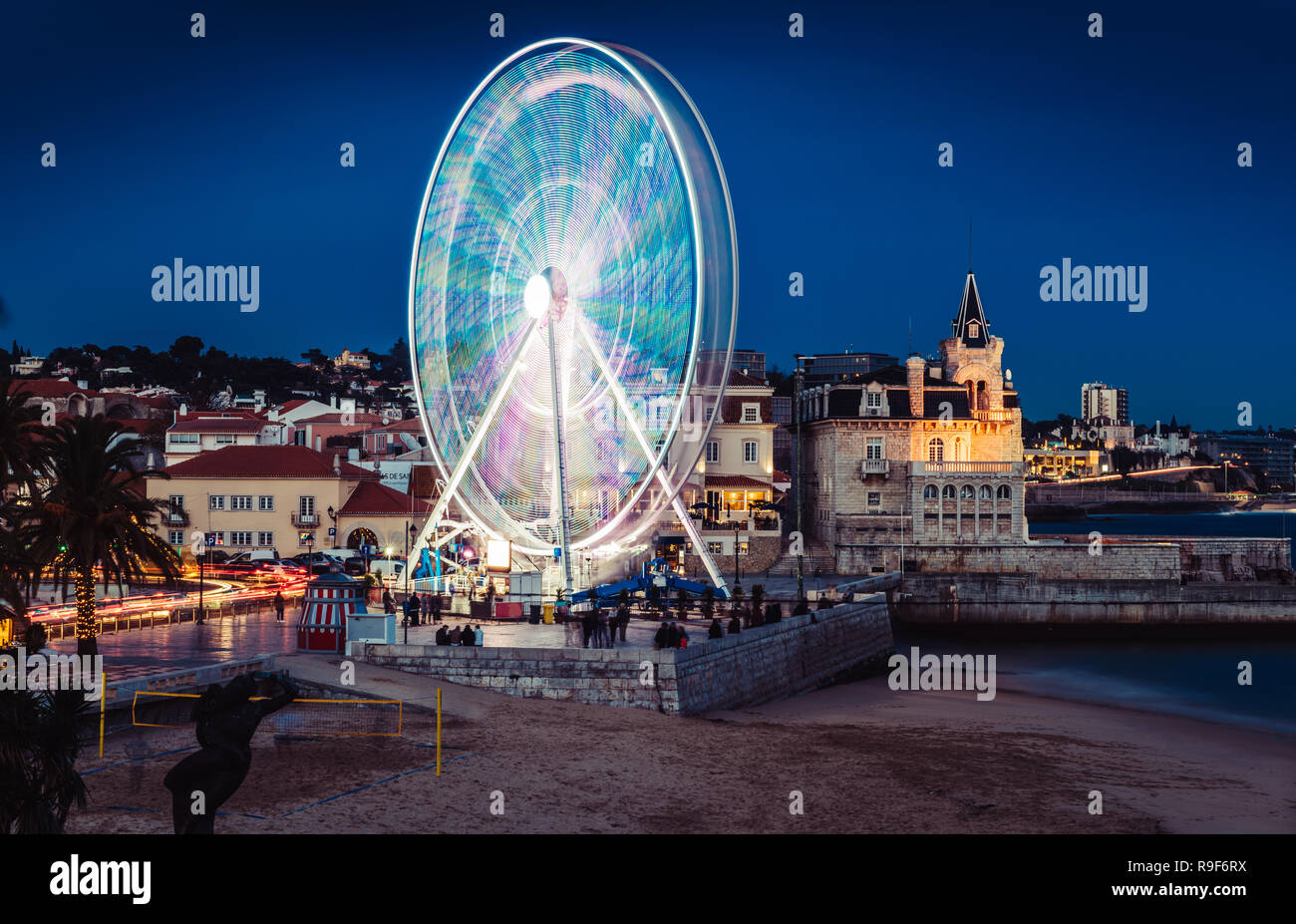 Long exposure of giant ferris wheel entertaining locals and tourists at Cascais Beach during the Christmas Season at night - Stock Image