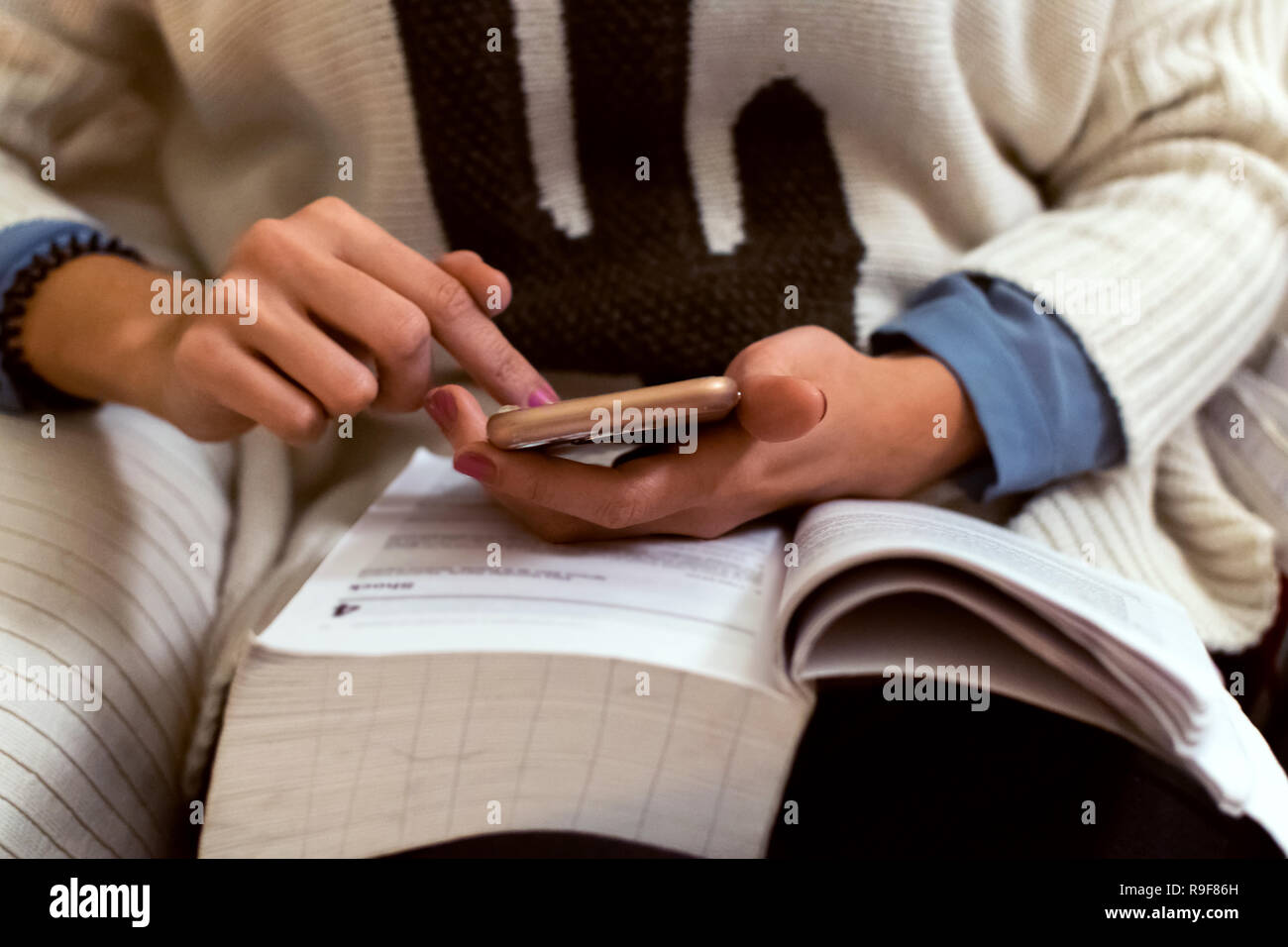 Student reading a book and using her phone at the same time. Technology and books. Low angle of woman - Stock Image