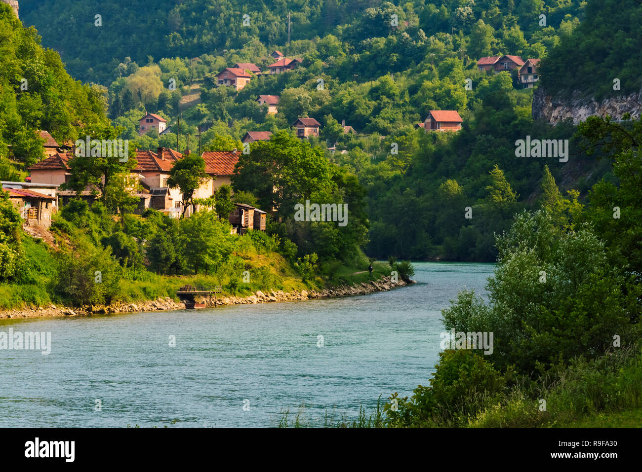 Houses and church on the riverbank of the Drina River, Visegrad, Bosnia and Herzegovina - Stock Image