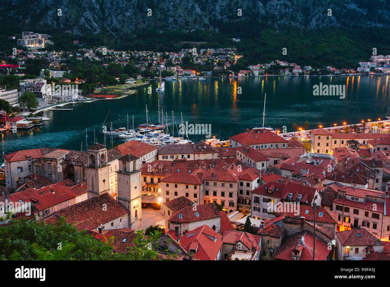 Red roof houses and boats on the Adriatic coast in the Bay of Kotor at dusk, Montenegro - Stock Image