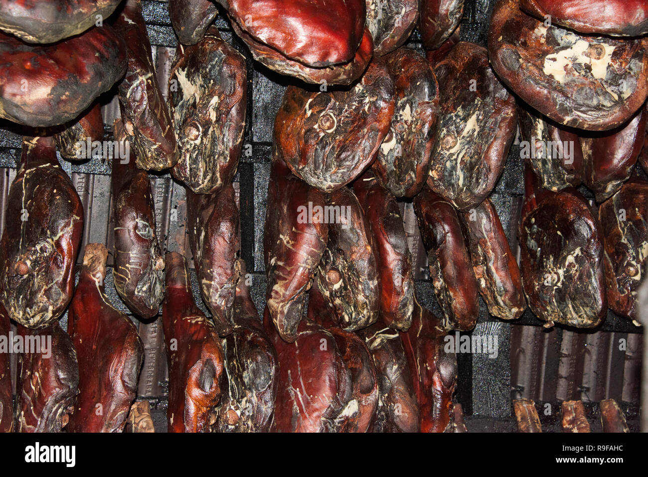 Drying ham inside an old house, Montenegro Stock Photo