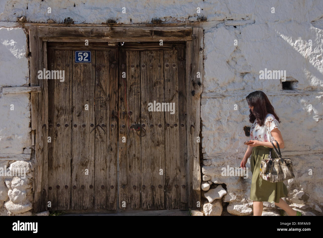 Woman passing by the wooden door of an old house, Prizren, Kosovo - Stock Image