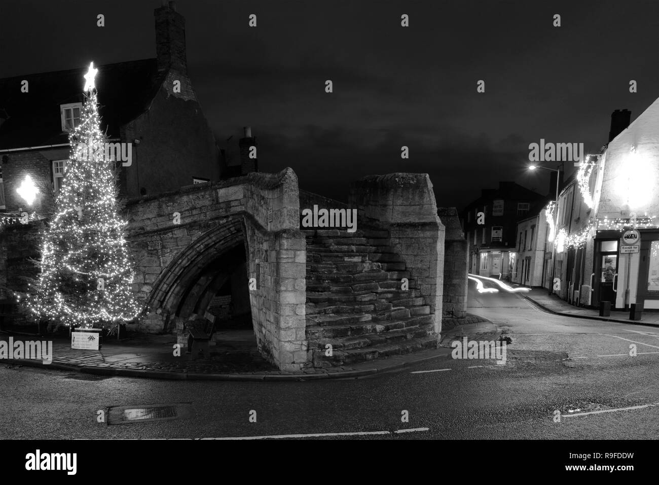 Christmas lights and tree, Trinity Bridge, a 14th Century three-way stone arch bridge, Crowland town, Lincolnshire, England, UK - Stock Image